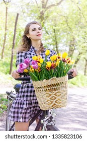 Beautiful woman on a bicycle with a bouquet of tulips in a basket