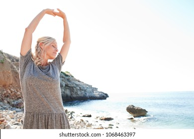 Beautiful woman on coastal rocky beach destination, awakening stretching arms up against sunny sky on summer holiday, nature outdoors. Healthy wellness living, leisure recreation lifestyle, exterior.