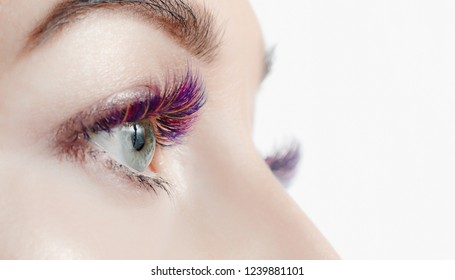 Beautiful woman on color eyelash extension procedure in spa salon. Concept fashion