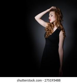 Beautiful  Woman on the Dark Background of Dark Wall