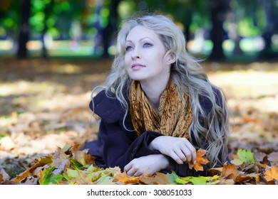 Beautiful woman on fallen leaves in autumn forest