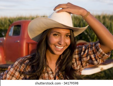 A beautiful woman on the farm with her old pickup truck
