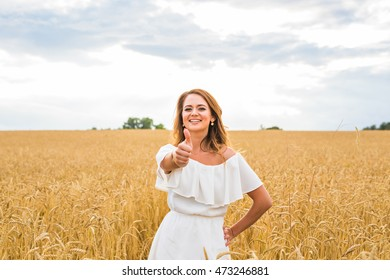 Beautiful woman on a field with thumbs up