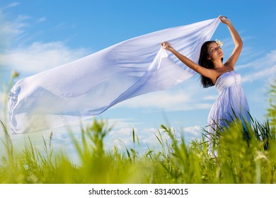 beautiful woman on green field wearing white dress