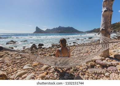 Beautiful woman on hammock on rocky shoreline with view of Hout Bay in Cape Town