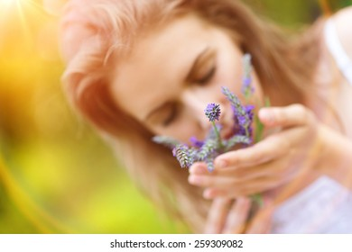 Beautiful woman on meadow holding lavender in her hands.