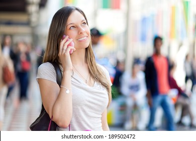 Beautiful woman on the phone in a crowded city street