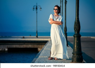 Beautiful woman on a pier on a summer day