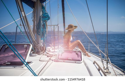 Beautiful woman on a sailboat enjoying the sun and the cool breeze of the ocean wind