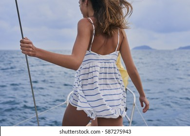 Beautiful woman on sailboat in ocean on luxury lifestyle happy adventure travel vacation