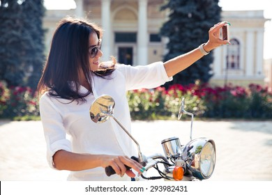 Beautiful woman on scooter making selfie photo on smartphone in old european town