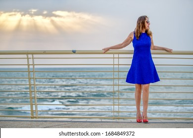 Beautiful woman on the seafront in Versilia with blue dress and red high heels