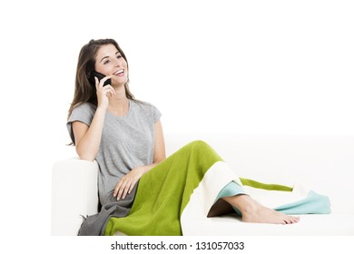 Beautiful woman on a sofa talking at cellphone, isolated over a white background