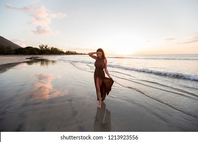 Beautiful woman on sunset background. Colorful dawn over the sea. Carefree woman enjoying the sunset on the beach. Happy lifestyle