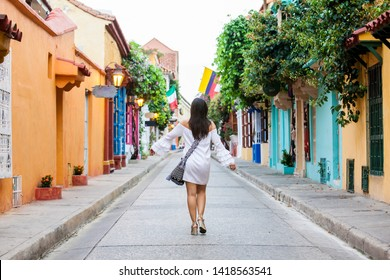 Beautiful woman on white dress walking alone at the colorful streets of the colonial walled city of Cartagena de Indias