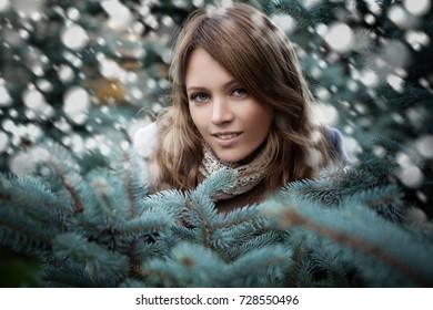 Beautiful Woman on Winter Background with Snow and Fir