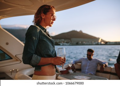 Beautiful woman with on yacht with drink. Woman partying on private boat with friends in background.