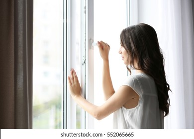 Beautiful woman opening window in the morning