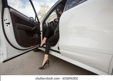 Beautiful woman opens the door and gets out of the car. Girl legs in high heels at the car in the city, urban