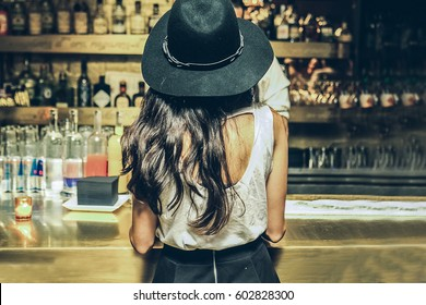 Beautiful woman is ordering a drink at the bar, view from the back