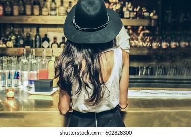 Mulher bonita está pedindo uma bebida no bar, vista da parte de trás