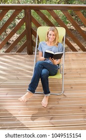 beautiful woman outdoor on chair reading