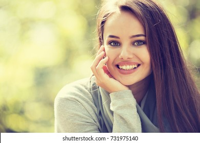 Beautiful woman outdoors in sunny day in autumn park. Portrait of an attractive happy girl