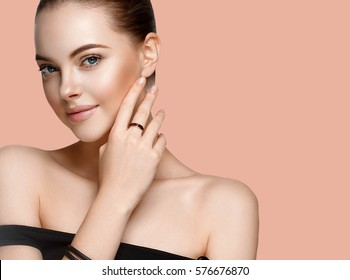 Beautiful woman over pink color background. Fashion Model jewelry