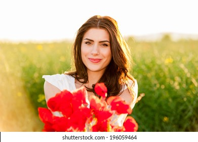 Beautiful woman over Sky and Sunset  in the field holding a poppies bouquet and smiling Free Happy Woman Enjoying Nature. Beauty Girl Outdoor.  Freedom concept. Series.