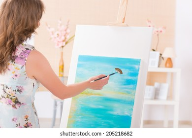 Beautiful woman painting on canvas at her home or workshop