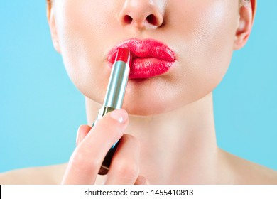 Beautiful woman paints lips with lipstick. Beautiful woman face. Makeup detail. Beauty girl with perfect skin. Red lips and health skin. The concept of beauty, glamor and passion