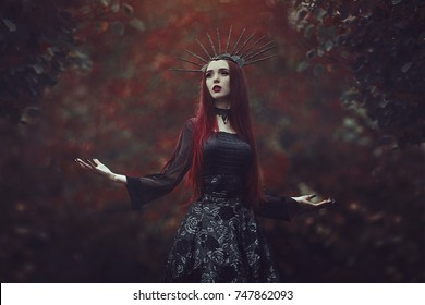 A beautiful woman with pale skin and long red hair in a black dress and in the black crownk. Girl witch with vampire claws and red lips. Gothic look. Outfit for halloween.