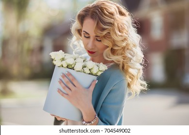Beautiful woman with paper box of flowers outdoor portrait on town  street