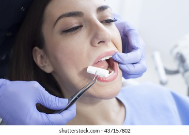Beautiful woman patient having dental treatment at dentist's office. Woman visiting her dentist