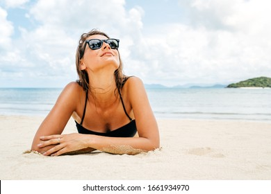 Beautiful woman with perfect body lying down on the beach sand, wearing black bikini and sunglasses, tanning on a beach resort, enjoying summer vacation