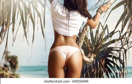 Beautiful woman with perfect body standing up on the beach, wearing stylish bikini,long hair, tanning on a beach resort, enjoying summer vacation,palms,sunshine,wet body,oil,coconuts.white t-shirt