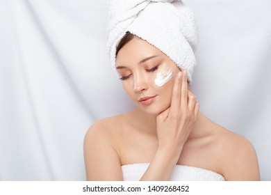beautiful woman with perfect clean skin applying cream on her face after bath, pretty girl in bath towel moisturizing cheeks