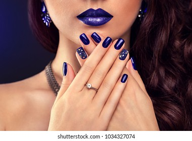 Beautiful woman with perfect make-up and blue manicure wearing jewellery on black background