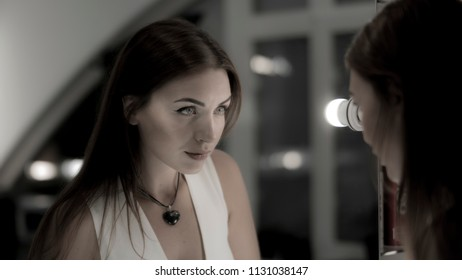 Beautiful woman with perfect makeup looking at mirror
