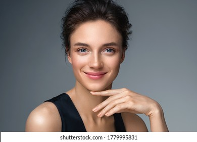 Beautiful woman with perfect makeup on gray background. Beauty and skin care concept