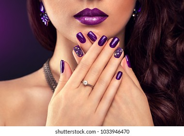 Beautiful woman with perfect make-up and purple manicure wearing jewellery on black background