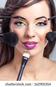 beautiful woman with perfect skin applying makeup