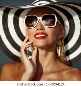 Beautiful woman with perfect skin in hat and sunglasses - close up portrait