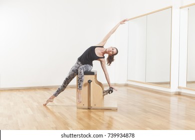 Beautiful woman performing pilates exercise, training on chair equipment