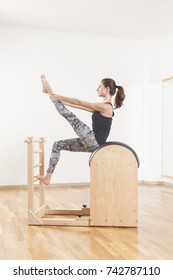 Beautiful woman performing pilates exercise, training on barrel equipment
