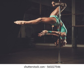 Beautiful woman performing pole dance on pole