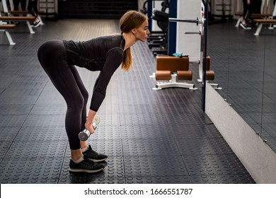 Beautiful woman performs Romanian deadlift in gym