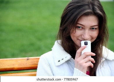 Beautiful woman with phone on the bench