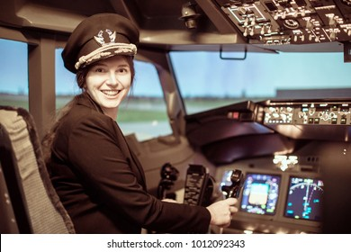 Beautiful woman pilot wearing uniform with epaulets, hat with golden wings sitting inside airliner. Girl looking at camera