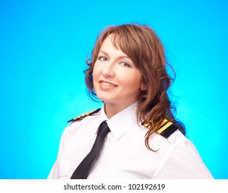 Beautiful woman pilot wearing uniform with epauletes standing on blue background.